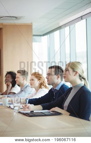 Business people sitting at conference table during meeting in board room