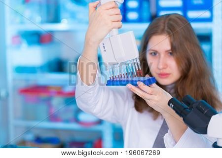 laboratory female assistant with pipette