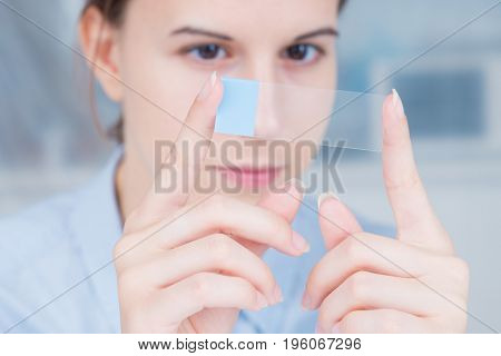 student girl with glass empty microscope slide in hand