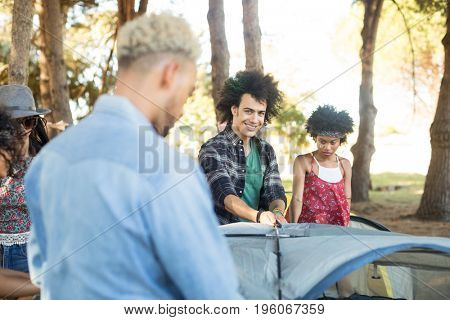 Smiling man with friends setting up tent at forest