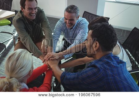 Happy business colleagues stacking hands while sitting on chairs by window at office
