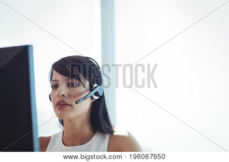 Young businesswoman wearing headset while working on computer at call center