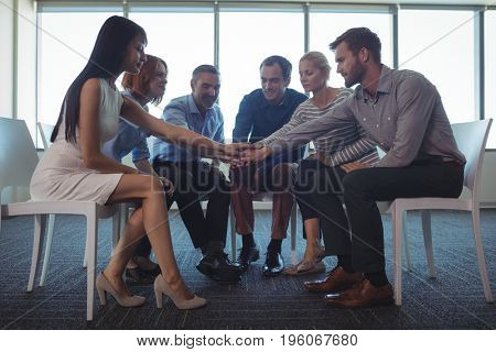 Business colleagues stacking hands while sitting on chairs in office