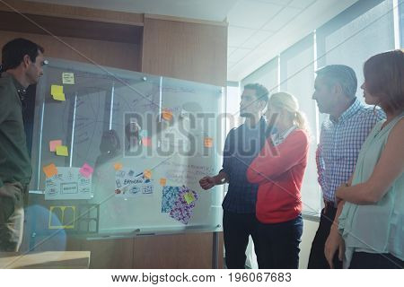 Business people discussing by notes on whiteboard at office