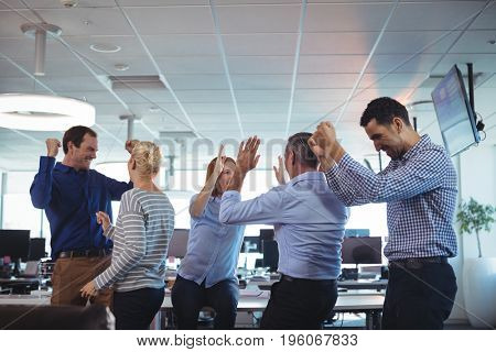 Cheerful business colleagues by desk at office
