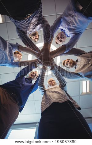 Directly below shot of business colleagues stacking hands against ceiling at office
