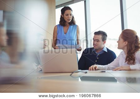 Colleagues discussing at desk during business metting in board room