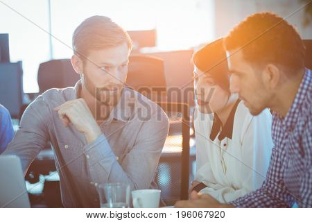 Focused business partners discussing at office desk in meeting