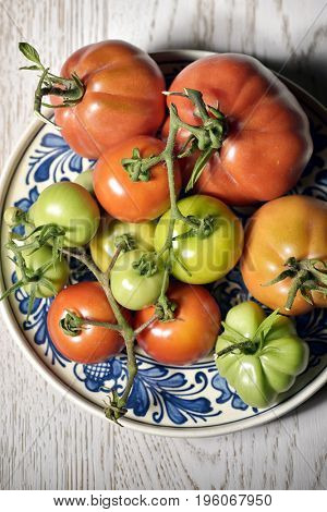 Fresh tomatoes on traditional plate