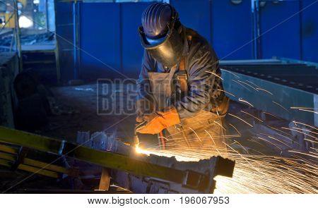 Welder work inside of construction plant