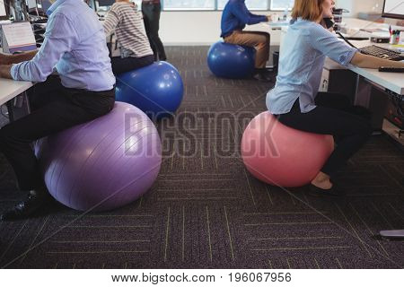 Low section of business people sitting on exercise balls while working at desk in office