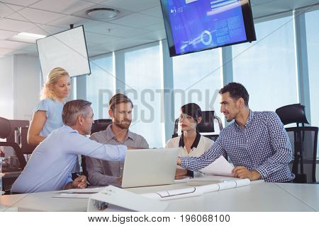 Business partners shaking hands at desk in office