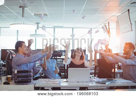 Cheerful business people tossing crumpled paper balls at desk in office
