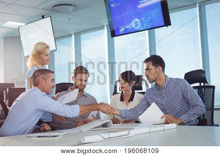 Business partners shaking hands in metting at office desk
