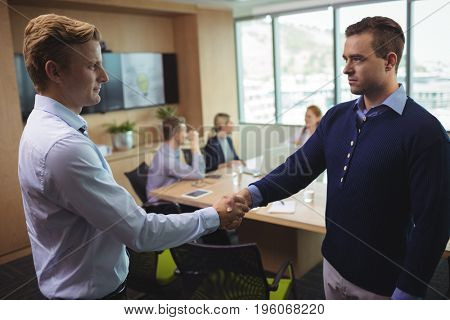 Business people shaking hands in board room during meeting