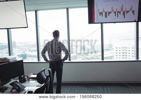 Rear view of businessman standing with hands on hip against window at office