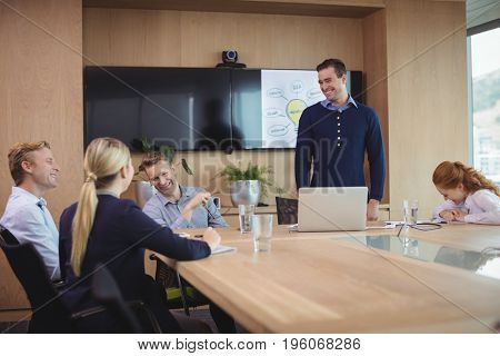 Happy business colleagues discussing during meeting in board room