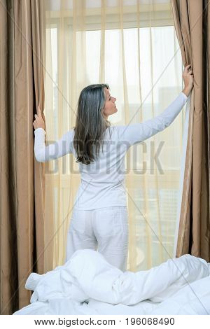 Mature woman is opening curtains in her bedroom in a hotel/apartment