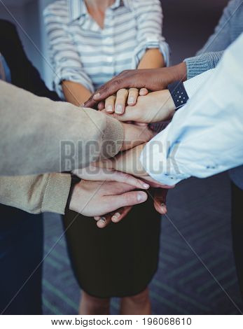 Business colleagues stacking hands at office