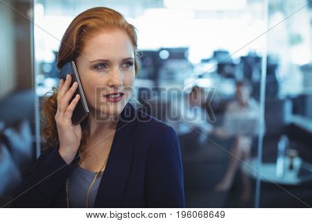 Thoughtful businesswoman taking on mobile phone at office