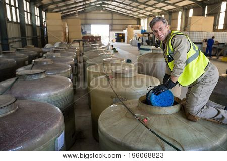 Portrait of happy worker removing oil from tank in factory