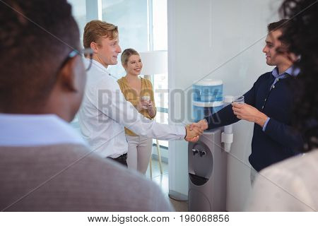 Business colleagues shaking hands while holding drinking glass at office