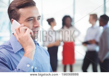 Businessman talking on mobile phone with colleagues discussing in background at office