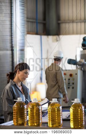 Female worker maintaining record while technician operating machine in factory