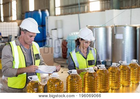 Workers checking records of oil bottles in factory
