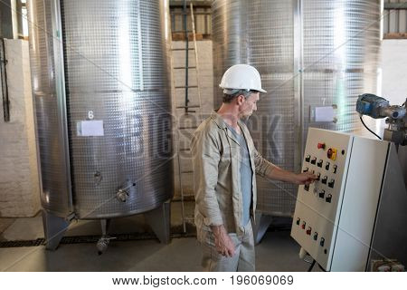 Attentive technician operating a machine in oil factory