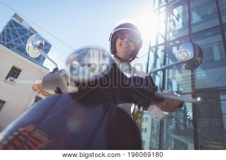 Low angle view of woman riding motor scooter on sunny day