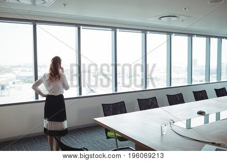 Rear view of businesswoman talking on mobile phone in board room
