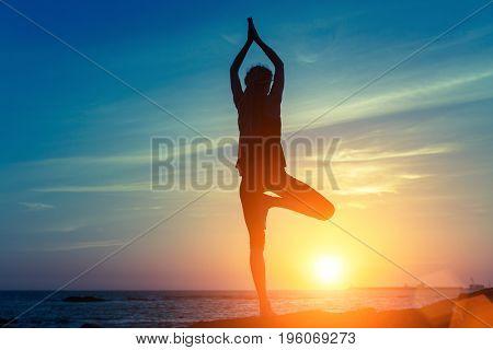 Silhouette of beautiful yoga woman standing on sea coast during beautiful twilight.