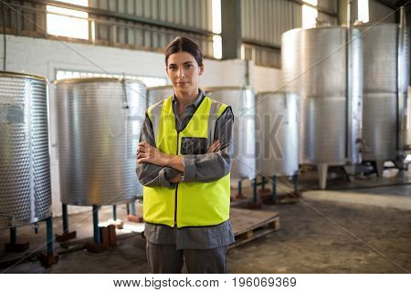 Portrait of confident technician standing with arms crossed in oil factory