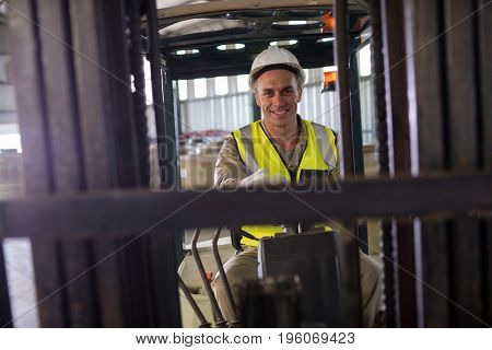 Portrait of worker driving forklift in oil factory