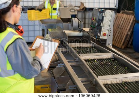 Female technician writing on clipboard in oil factory