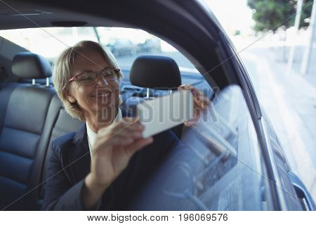 Businesswoman photographing while traveling in car