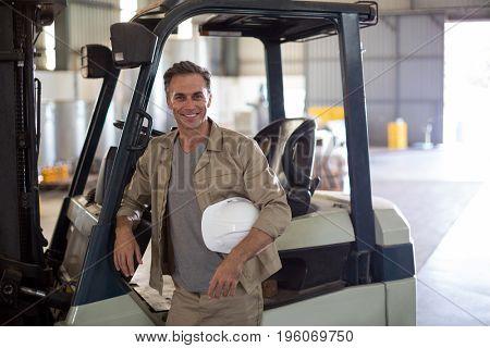 Portrait of happy worker standing near forklift in oil factory