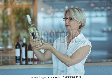 Businesswoman looking at winebottle while standing in office