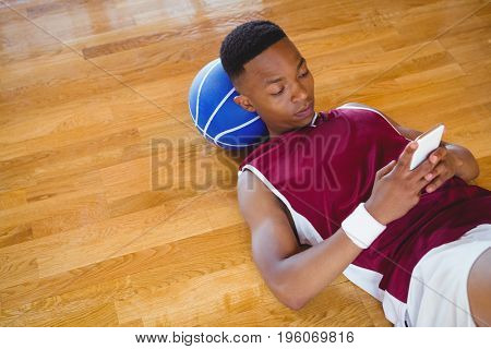 High angle view of male basketball player using mobile phone while lying on floor in court