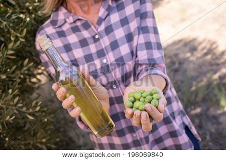Woman holding olive oil and harvested olives in farm