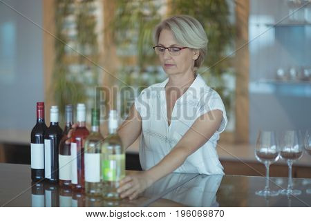 Businesswoman arranging winebottles on table in office
