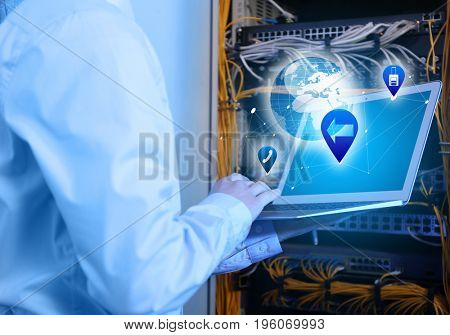 Concept of management information systems. Young engineer with laptop in server room