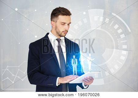 Concept of management information systems. Young man using tablet on light background