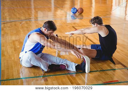 High angle view of male friends exercising while sitting on floor in court