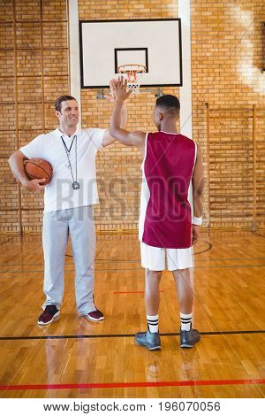 Coach high fiving with basketball player while standing in court