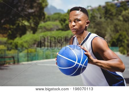 Male teenager holding basketball while practicing in court
