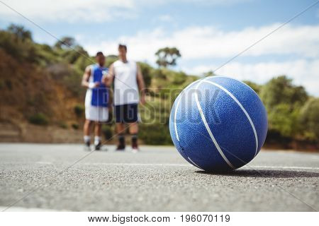 Blue basketball on ground with player standing in background at court