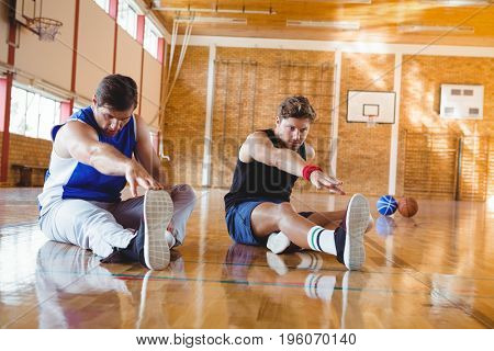 Full length of male friends exercising while sitting on floor in court