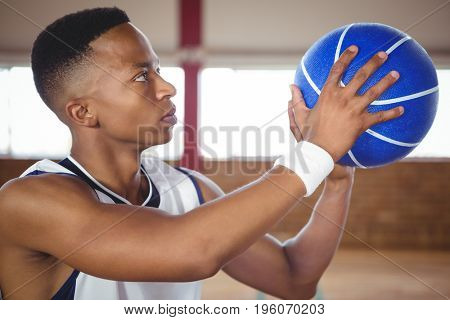 Close up of teenager practicing basketball in court